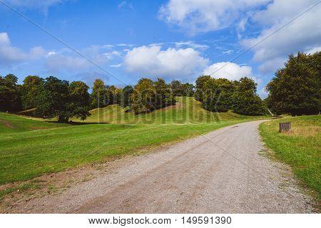 Green meadow, hills, oak trees and cloudy sky landscape in Jaegersborg. Forest park near Klampenborg, Copenhagen.