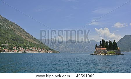 The tiny St George's Island in Kotor Bay Montenegro also known as the Island of the Dead. The island contains a 12th century Benedictine abbey and a cemetery. The village of Perast can be seen on the coast in the background