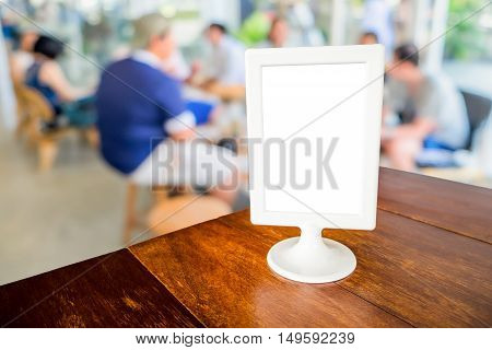 Mock up menu frame on wooden table in cafe or restaurant interior background Customer at cafe blur background concept with bokeh.