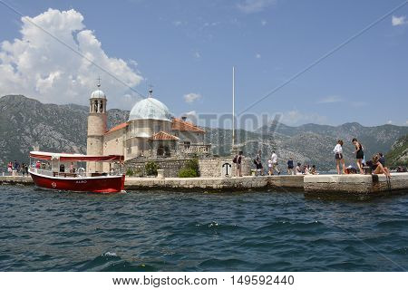 Perast Montenegro - June 27th 2016. Tourists visit the tiny man-made island of Ou Lady of the Rock off the coast of Perast in Kotor Bay at the stat of the tourist season.