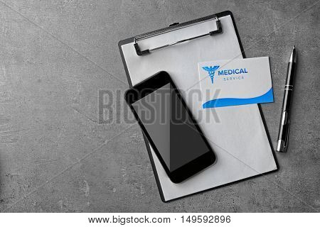 Medical service concept. Visiting card, clipboard and cellphone on grey background
