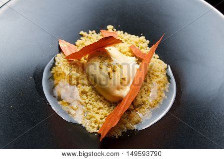 Apricot ice cream with elderberry in a black bowl.