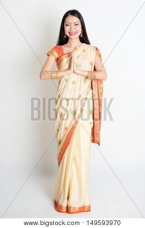 Full length mixed race Indian Chinese female with sari dress in greeting gesture, standing on plain background.