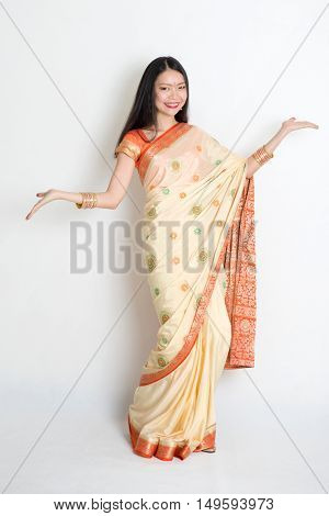 Portrait of young mixed race Indian Chinese woman in traditional sari dress dancing, on plain background.