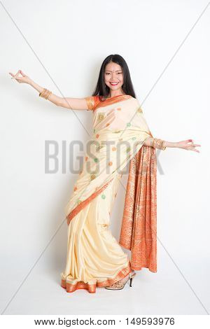Full length portrait of young mixed race Indian Chinese woman in traditional sari dress dancing, on plain background.