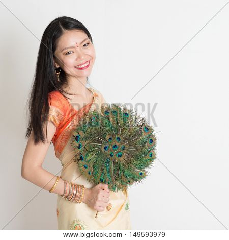 Portrait of young mixed race Indian Chinese woman in traditional sari dress, holding peacock feathers fan and looking at camera, on plain background.