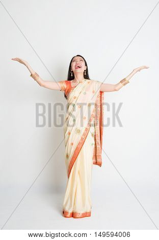 Portrait of young mixed race Indian Chinese woman in traditional sari dress hands raised looking upwards and smiling, full length on plain background.