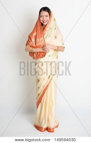 Portrait of young mixed race Indian Chinese woman in traditional sari dress smiling and looking at camera, full length on plain background.