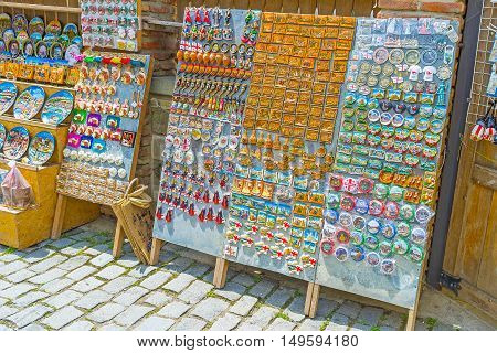 MTSKHETA GEORGIA - JUNE 6 2016: The board with the fridge magnets toys and bottle-openers in tourist market stall offering various souvenirs of local origin on June 6 in Mtskheta.