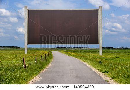 Big blank billboard on a roadside with blue sky