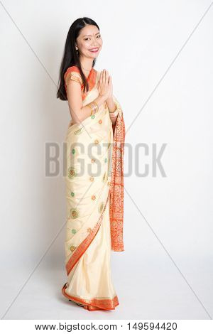 Full length mixed race Indian Chinese girl with sari dress in greeting gesture, standing on plain background.