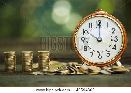 Alarm clock and money coins - time is money concept