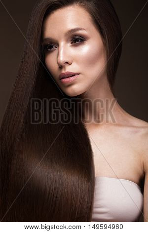 Beautiful brunette girl with a perfectly smooth hair, and classic make-up. Beauty face. Picture taken in the studio.