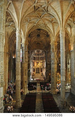 Lisbon, Portugal - October 21, 2014. Interior of the church of Mosteiro dos Jeronimos in Lisbon, with view toward the Main Altar, columns, benches and people.
