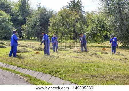 MOSCOW RUSSIA - August 18.2013: Migrant workers clean grass clippingson the lawn in the park Kolomenskoye