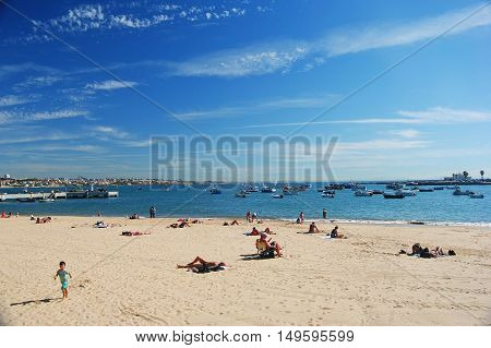 Cascais, Portugal - October 23, 2014. Praia da Ribeira beach in Cascais, with people and boats out in the sea.