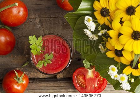 Glass of tomato juice and fresh tomatos on old wooden table decorated with yelow flowers