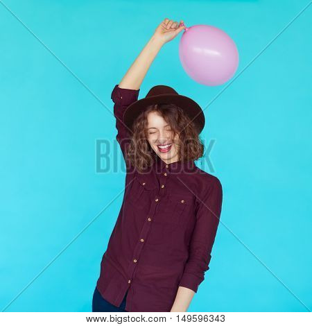 Casual lifestyle with beautiful hipster girl holding a pink balloon and smiling against blue background, isolated.