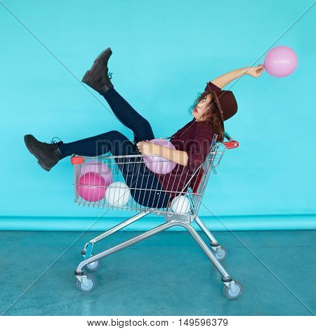 Beautiful brunette girl sitting in shopping cart over a blue background, color balloons in her one hand