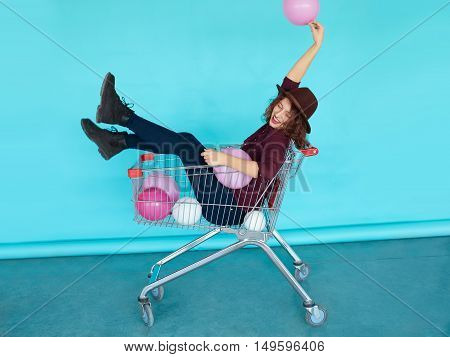 Young funky woman sitting in shopping cart over blue color wall. Naughty girl having fun. Indoors, lifestyle