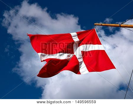 Flag of Denmark up high in the air with clear blue sky background