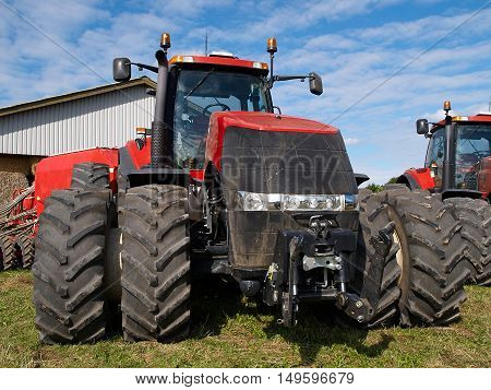 Agricultural giant modern red tractor in a big farm
