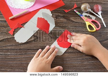 The Child Create A Greeting Packaging For Candy Santa Claus On Paper, Glue On The Details Of The Pap