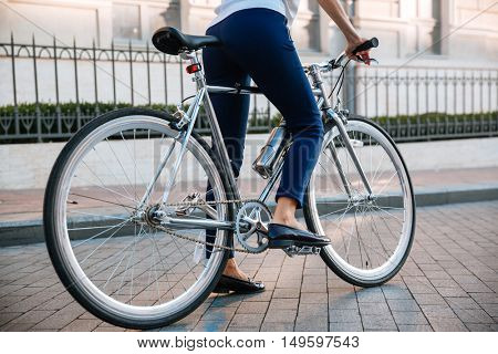 Cropped image of a female biker riding bicycle on the street