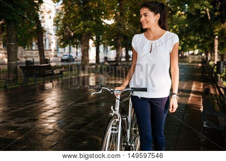 Casual brunette smiling girl walking at the city park with bicycle