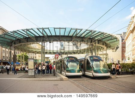 STRASBOURG FRANCE - APR 7 2016: Busy center of the French city of Strasbourg Alsace with two tramways and lots of commuters pedestrians walking under architectural station l'Homme de Fer