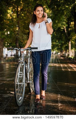 Full length portrait of a happy cheerful girl with mobile phpne and bicycle