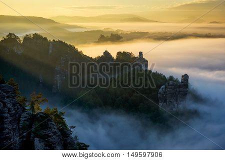 Foggy Sunrise At Bastei, Saxon Switzerland, Germany. Beautiful Morning With Amazing Rocks And Deep F