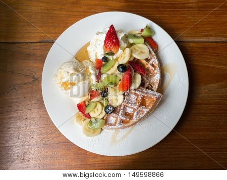 Mixed fruits waffle with ice cream wooden table