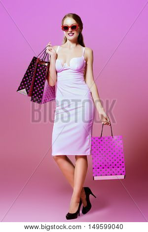 Glamorous young woman in elegant fitting dress and sunglasses alluring with shopping bags. Beauty, fashion concept. Evening dresses collection. Seasonal sale.