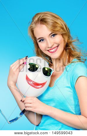 Pretty cheerful young woman in summer clothes posing with a balloon and sunglasses.