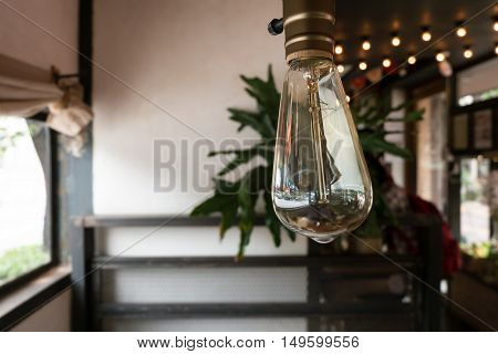 Edison style light bulb with its reflection in cafe.
