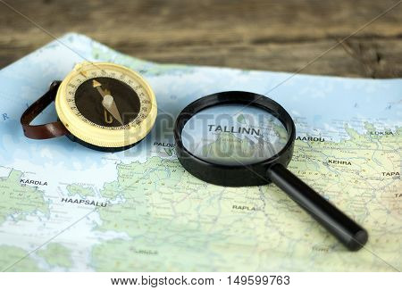Compass and magnifying glass on the map Estonia. Authentic and rustic lens and compass. Selective focus. Blurred vision. Tallinn city.