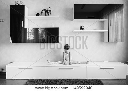 little girl sitting on twine (split) on furniture
