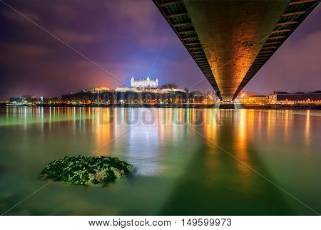 Bratislava castleparliament and Danune river in capital city of SlovakiaBratislava. Beautiful night reflection during winter time.