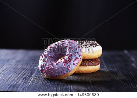 Close view at three tasty donuts with blue, chocolate and vanilla icing on a dark wooden background. With copy space.