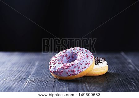 Donuts With Blue And Vanilla Icing On A Dark Background