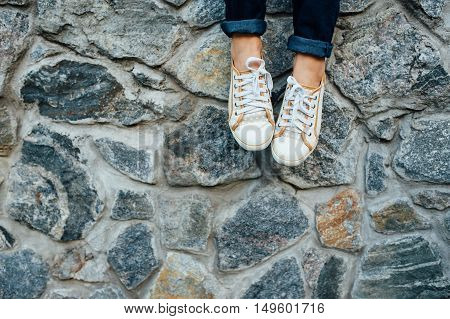 Woman's Legs With Sneakers Seated In Stone Wall.