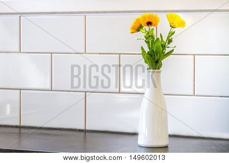 beautiful fresh flowers near kitchen wall of white ceramic tales