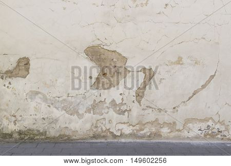 Old abandoned grunge wall and road pavement background texture in the city