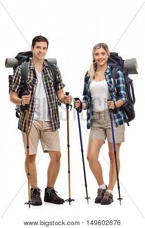 Full length portrait of a male and a female hiker posing with hiking equipment isolated on white background