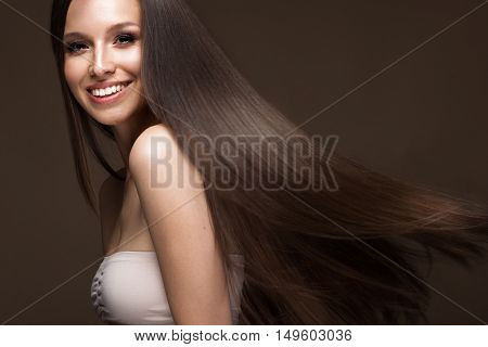 Beautiful brunette girl in move with a perfectly smooth hair and classic make-up. Beauty face. Picture taken in the studio.