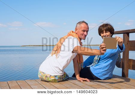 Couple enjoying life taking selfie using tablet pc on the sea coast. Happy people on the vacation.