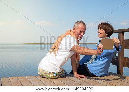 Joyful couple having fun taking selfie using tablet pc on the sea coast. Happy people on the vacation.