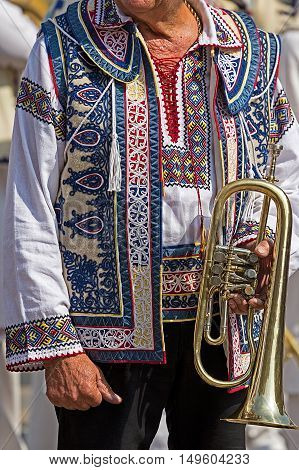 Detail of traditional Romanian folk costume worn by old singer man from Banat area Romanian. Trumpet as musical instrument is used on this area.