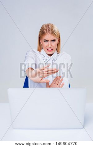 Young businesswoman working at laptop computer. hiding behind the monitor. frustrated, spiteful woman in shock